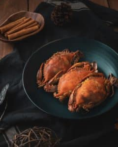 A plate of three crabs on a wooden table with cinnamon sticks and a pine cone nearby.