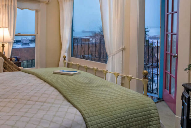 Painted brass bed made up in white and green faces an open door to a wrought iron balcony.