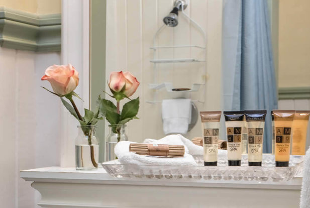 Shelf in a bathroom with a rose in a vase and a tray of travel-size toiletries.