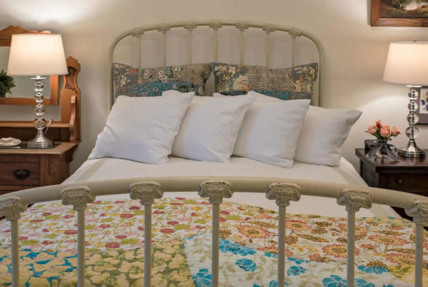 Painted metal bed made up in a bright quilt with fluffy pillows, a wooden nightstand and a wooden dresser.