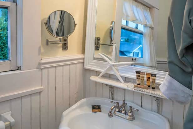 Bathroom with white chair rail, a large window, and a pedestal sink in white with a mirror.