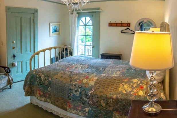 Peaceful room with wrought iron bed in a colorful quilt, green doors, and glass-based lamps.