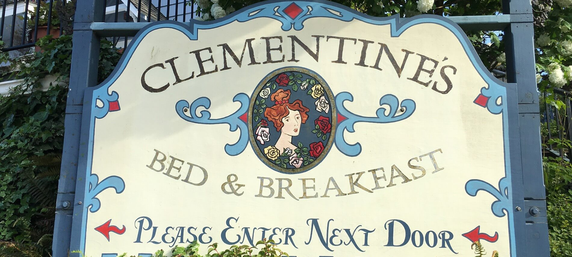 Large wooden sign with a blonde Victorian woman that says Clementine's Bed & Breakfast - Please Enter Next Door.