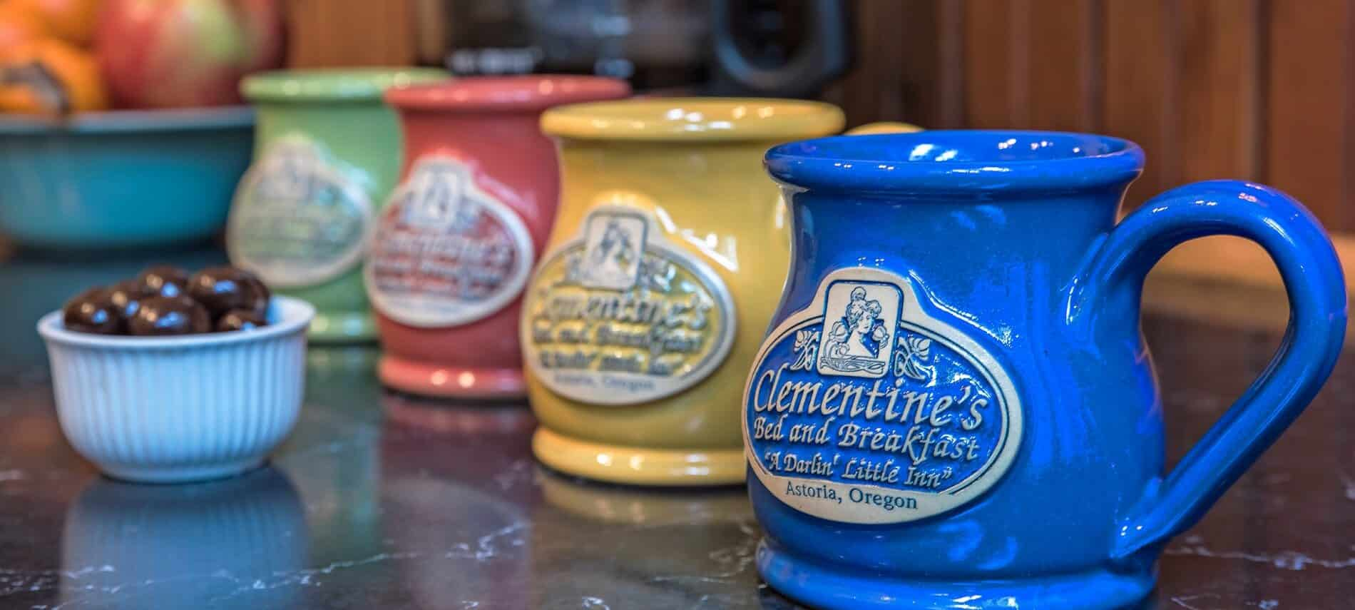 Row of brightly colored stoneware mugs with the Clementine's Bed and Breakfast logo.