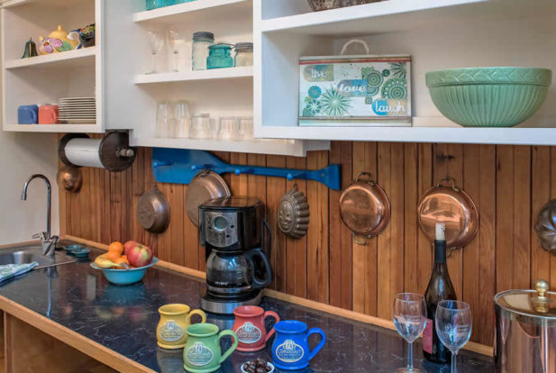 Kitchen cabinet with a coffee station surrounded by colorful stoneware mugs and copper accents.