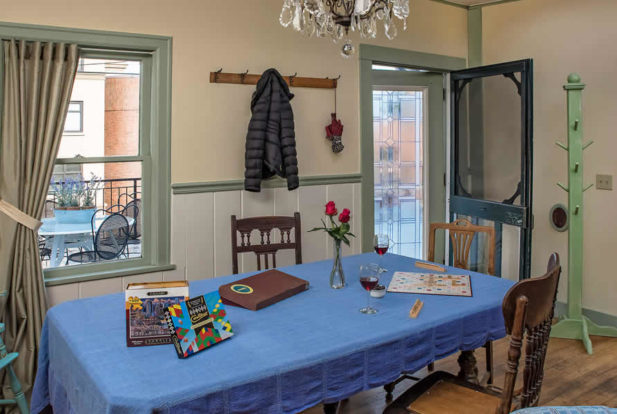 Large table with a blue cloth set up with board games in a room with wooden floors and a door out to the porch.