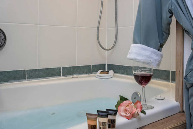 Large bathtub filling up with water with a glass of wine, toiletries and a rose on the edge.