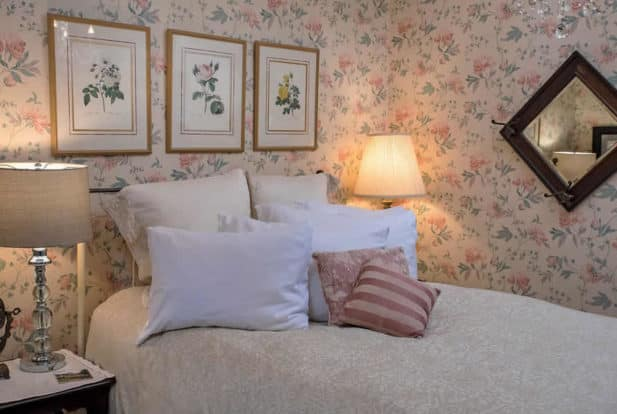 Metal frame bed made up in white with fluffy pillows, in a bedroom with pink and cream rose wallpaper.