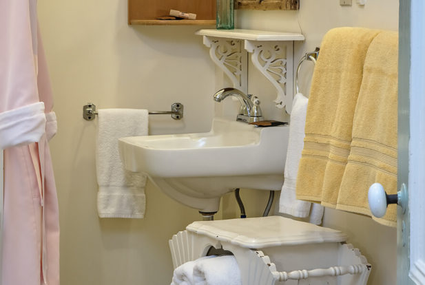 Bathroom with a white sink, pink shower curtain and yellow and white towels.