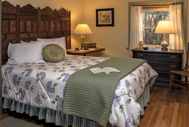 Large bed with an ornate headboard, made up in white, green and lavender, in a roomw ith a dresser and chair.