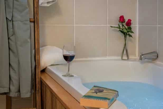 White bathtub inset framed in wood, full of water with a book, glass of wine and two roses in a vase on the edge.
