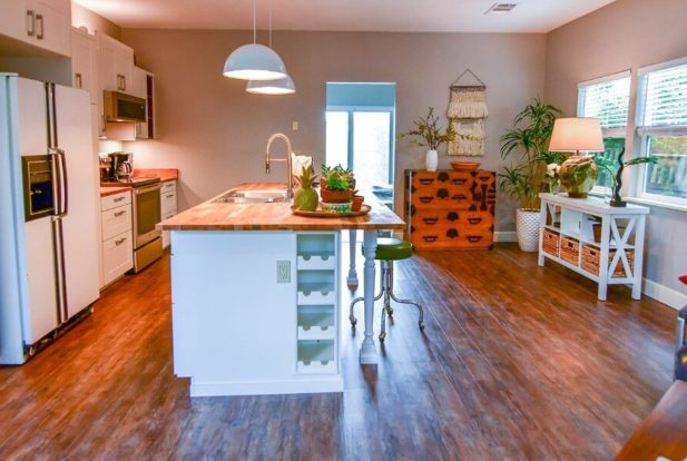 Spacious kitchen with large island with butcher block counter top and white cabinets.
