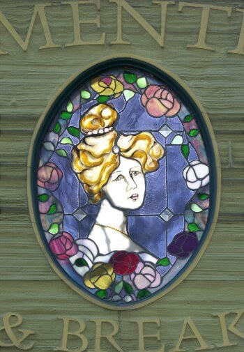Wooden sign made to look like stained glass of a blonde Victorian woman surrounded by flowers.