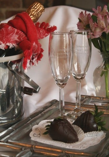 Sliver champagne bucket next to a silver tray holding two champagne flutes and chocolate covered strawberries.