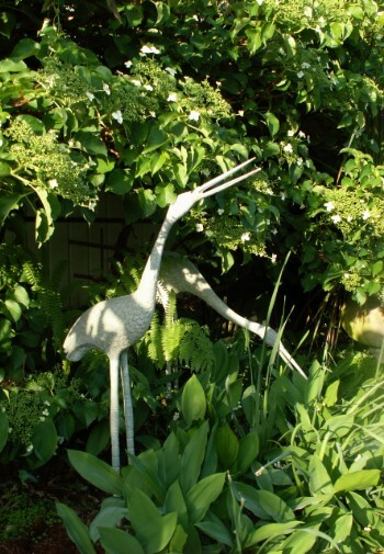White crane statues surrounded by green plants in a garden.