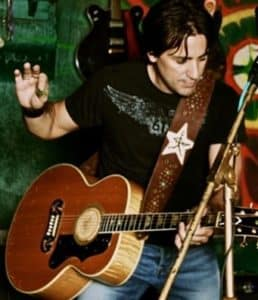 Musician Steve Azar playing the guitar and holding his pick up in the air.