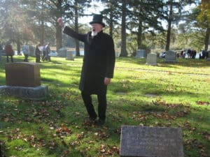 Matt Hensley portrays Captain Moses Rogers in the Ocean View Cemetery. He is wearing a black suit, black top hat, and is raising his hand.