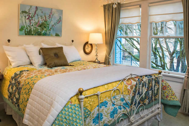 Painted brass bed made up with a colorful quilt and lots of pillows in a bedroom painted pale yellow.