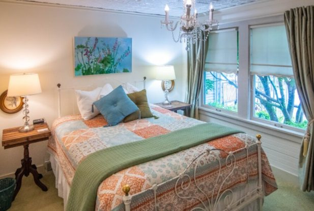 Bright bedroom with a white wrought iron bed covered in an orange paisley comforter